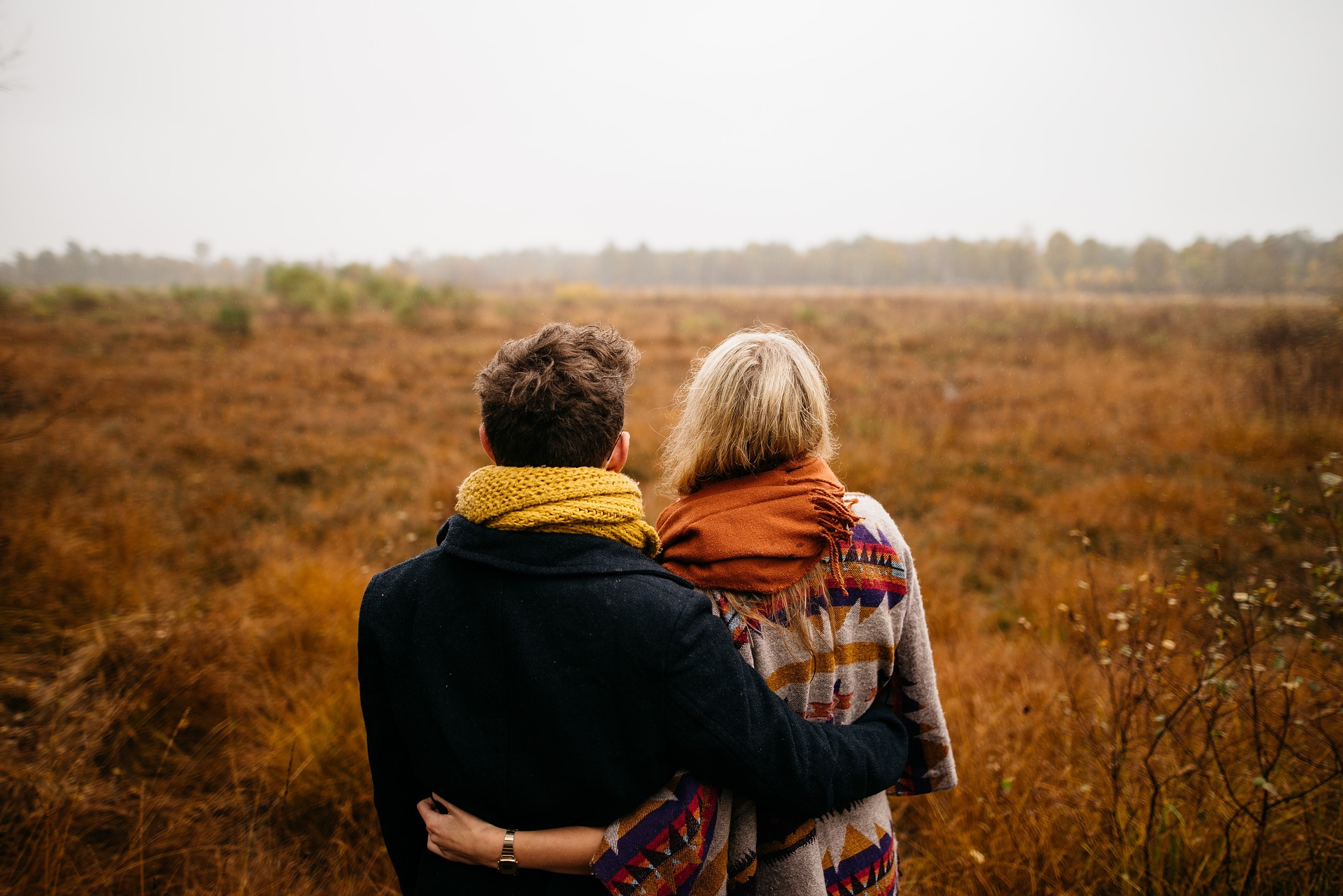 Picture of a couple holding each other, looking at a field