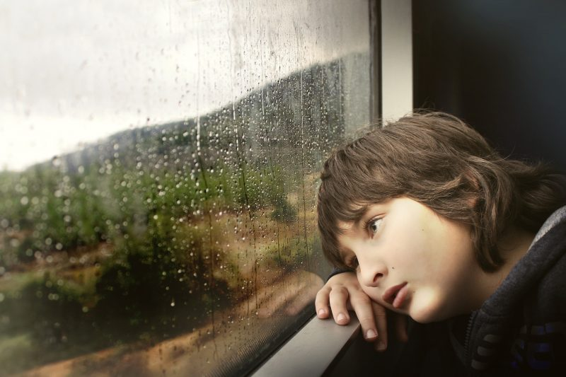 sad child staring out window
